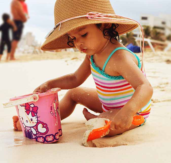 Kid playing in the sun with a hat