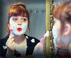 a woman shaves her face