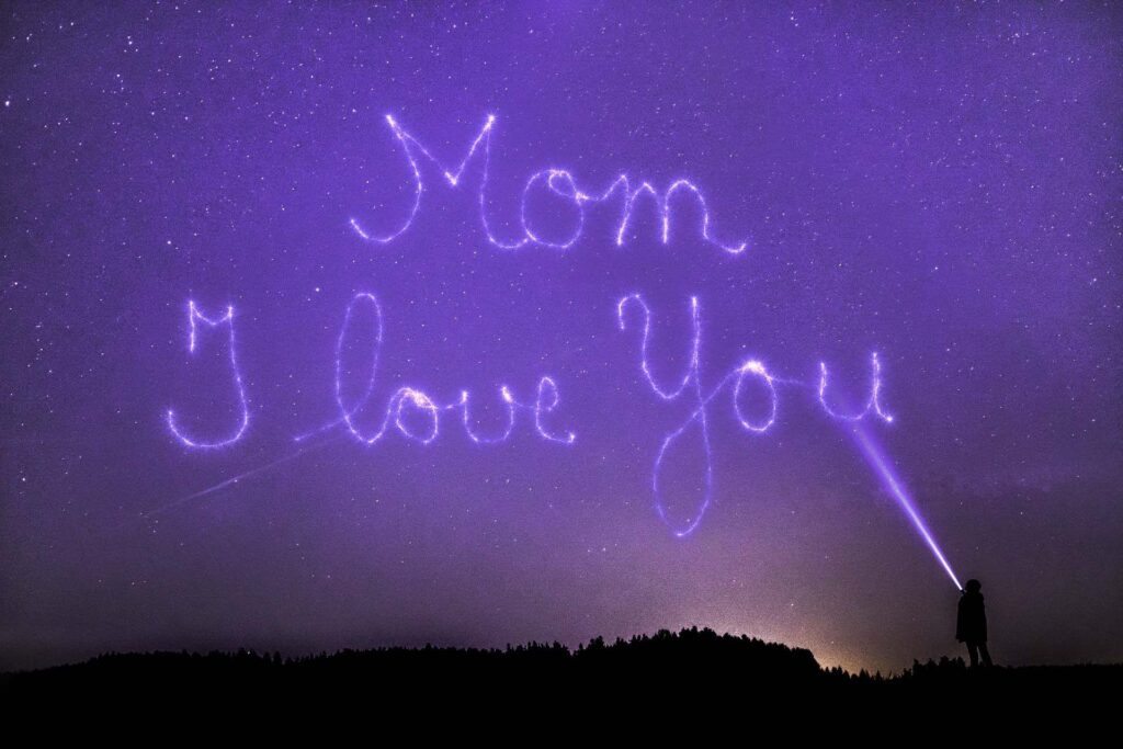 a kid is writing mom i love you with a torch